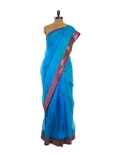 Striking Blue Super Net Saree With Purple Zigzag Border - Pothys